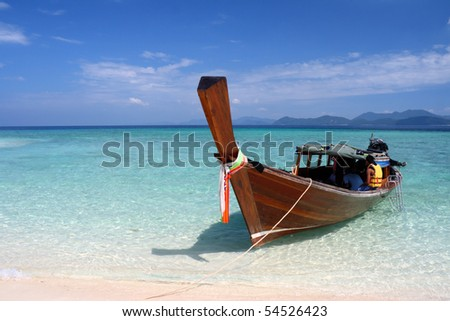 Long tail boat moored to shore, crystal clear water of Andaman Sea, Thailand