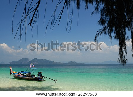 Long tail boat on a tropical island - stock photo