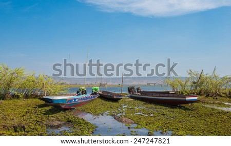 long-tail boat on the lake bank - stock photo
