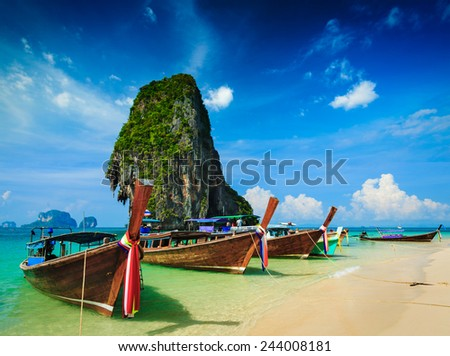 Long tail boat on tropical beach with limestone rock, Krabi, Thailand - stock photo