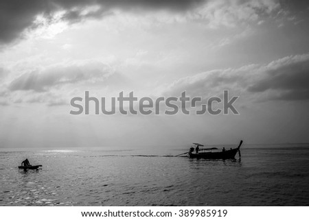 Long-tail boat under beautiful sun rays at sunset in gorgeous Maya bay, Phi-Phi, Thailand. Black and white image with selective focus - stock photo