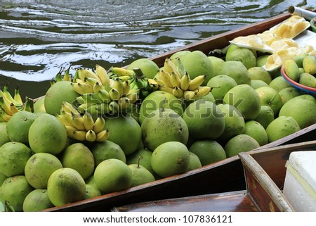 long-tail boat with fruits on the floating market