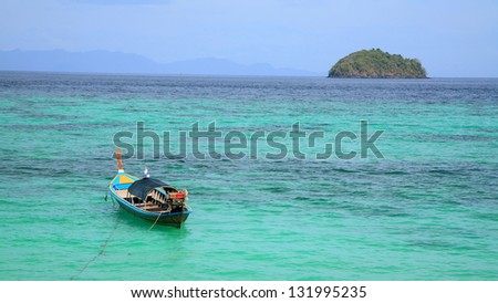 Long tail wooden boat on crystal  turquoise Andaman sea at Koh Lipe in Satun, Thailand