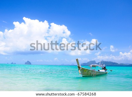 Long tailboats by the shore at kradan Island, Trang Thailand against beautiful clear blue sky/Tailboat by the shore at kradan Island - stock photo