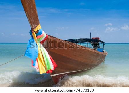 Long tailed boat on a wave at Phi Phi island, Thailand