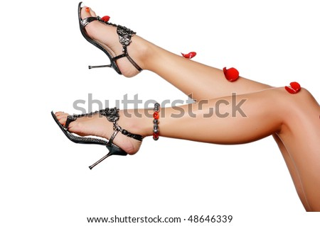 long, tanned legs girls covered with rose petals isolated on white background - stock photo