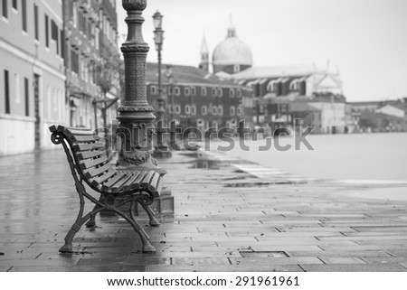 long time exposure of typical wooden bench on promenade in Venice (Venezia) on a rainy day in autumn without people, Italy, Europe, black and white - stock photo