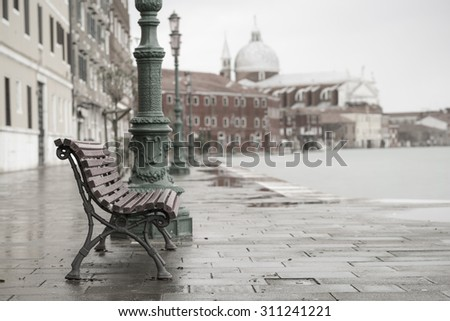 long time exposure of typical wooden bench on promenade in Venice (Venezia) on a rainy day in autumn without people, Italy, Europe - stock photo