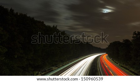 long time exposure on a highway with car light trails and moon in the sky - stock photo