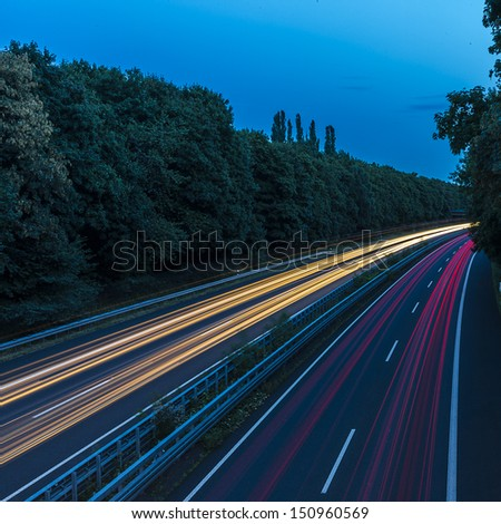 long time exposure on a highway with car light trails at blue hour - stock photo