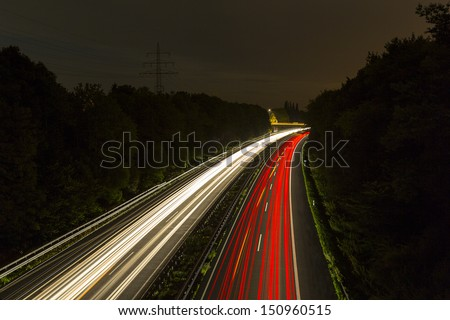 long time exposure on a highway with car light trails at night - stock photo