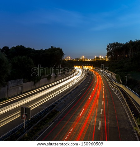 long time exposure on a highway with car light trails on blue hour - stock photo