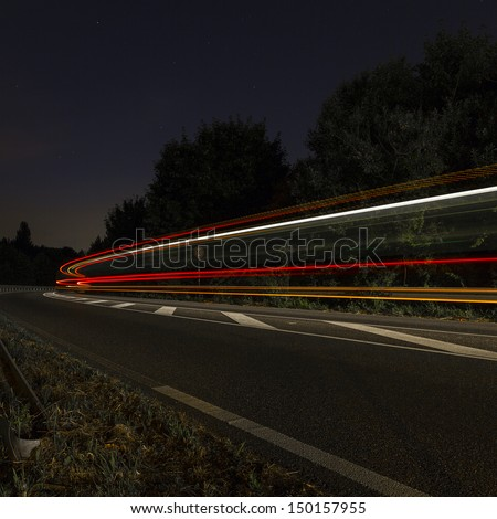long time exposure on a roadway with car light trails - stock photo