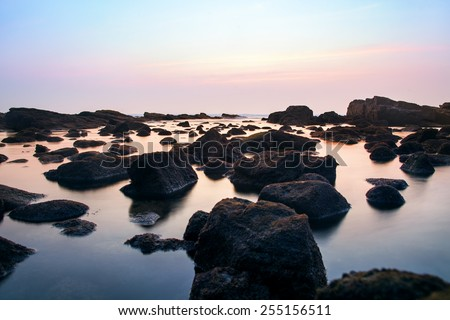 Long time exposure photo of rocks in the sea. - stock photo