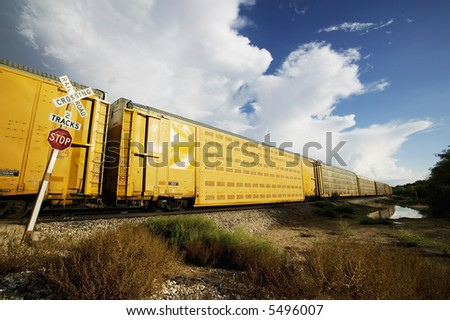 Long train stopped at a crossing with a dramatic sky. - stock photo