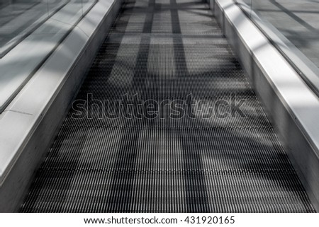 Long walkway of escalator. On the steps of the visible shadows of the handrail. - stock photo