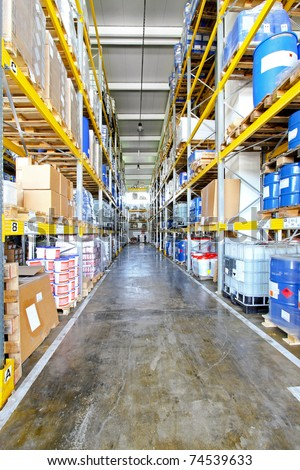 Long warehouse corridor with barrels and boxes - stock photo