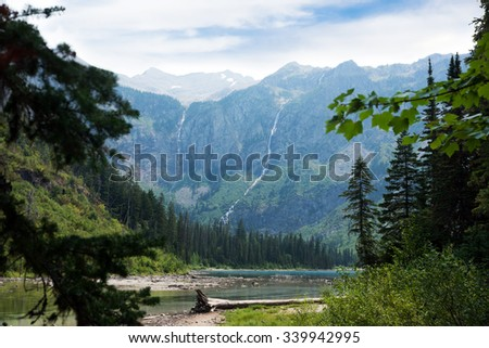Long waterfalls cascading  down steep mountain sides into Avalanche Lake, Glacier National Park - stock photo
