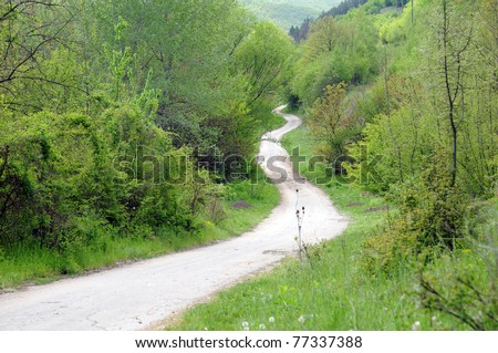 Long winding dirt road in the Balkan Mountains in Bulgaria in the spring. - stock photo