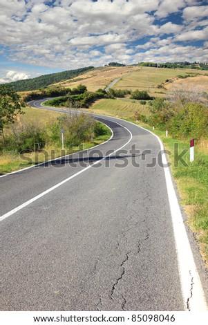 long winding road trough tuscany hills - stock photo