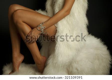 Long woman legs isolated on white fur coat . Luxury jewelry and white fur. Studio shot. Horizontal photography - stock photo