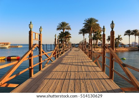 Long wooden boardwalk with lamposts on a sunny day in Hurghada, Egypt