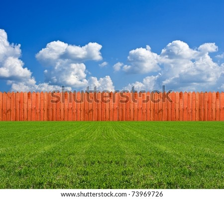 long wooden fence in a green field - stock photo