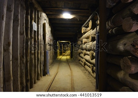 Long wooden hallway in mineshaft  with railroad tracks - stock photo