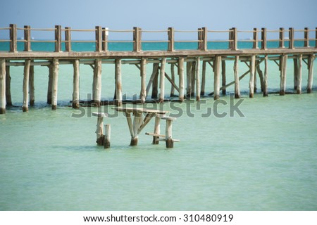 Long wooden jetty in the sea from a tropical island lagoon on beach - stock photo