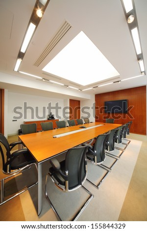 Long wooden table, black armchairs and tv in light room for business meetings.