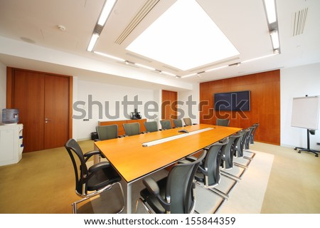 Long wooden table, black armchairs in light room for business meetings.  - stock photo