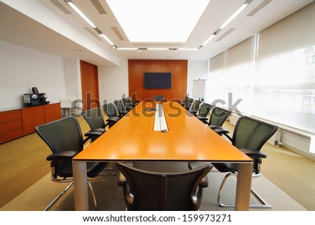 Long wooden table, modern armchairs and tv in light room for business meetings.  - stock photo