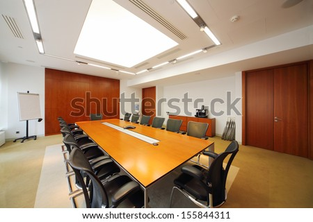 Long wooden table, modern armchairs in empty room for business meetings.  - stock photo