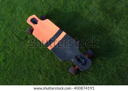 longboard grass green. Black and orange longboard on a green lawn grass