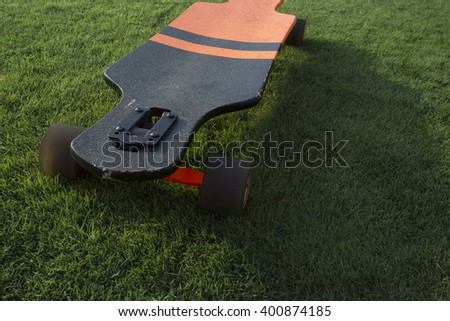 longboard green grass. Black and orange longboard on a green lawn grass