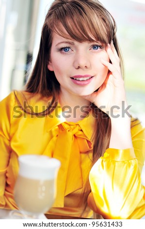 longhaired girl drinking big cup of latte in cafe - stock photo