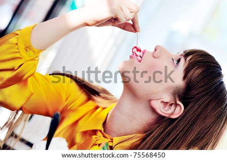 longhaired girl enjoying dessert with cherry in  cafe - stock photo