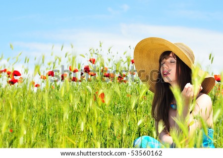 longhaired girl wearing straw hat relaxing in field - stock photo