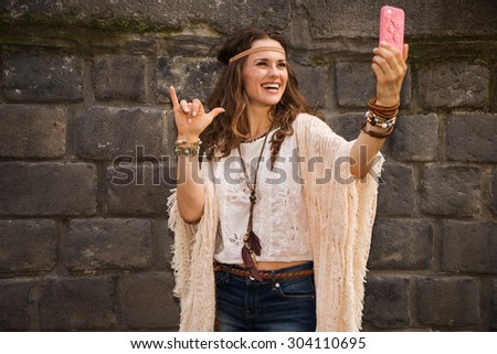 Longhaired hippy-looking young lady in jeans shorts, knitted shawl and white blouse standing near stone wall in old town and making selfie - stock photo