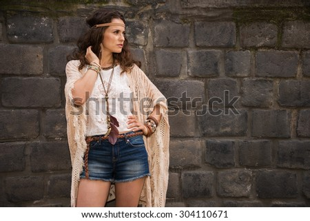 Longhaired hippy-looking young lady in jeans shorts, knitted shawl and white blouse stands near stone wall in old town looking away - stock photo
