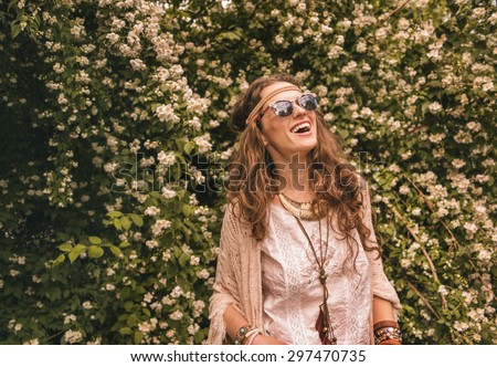 Longhaired hippy-looking young lady in knitted shawl and white blouse standing among flowers and looking up on copy space - stock photo