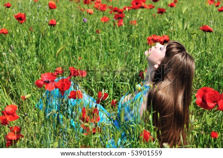 longhaired romantic young woman resting in poppy field - stock photo