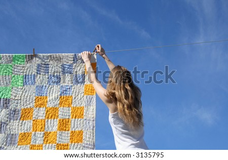 Longhaired young woman putting a bright counterpane on a clothes-line to dry in a breeze. - stock photo