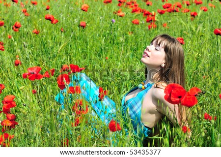 longhaired young woman resting in poppy field - stock photo