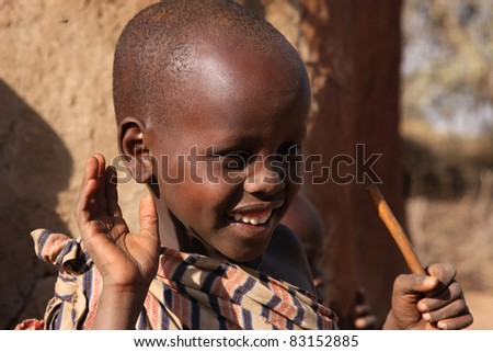 LONGIDO, TANZANIA -  JULY 18: Unidentified child welcomes tourists in his village, on July, 18, 2011 at Longido, Tanzania. The Masai people are the most famous nomadic tribe in Africa. - stock photo