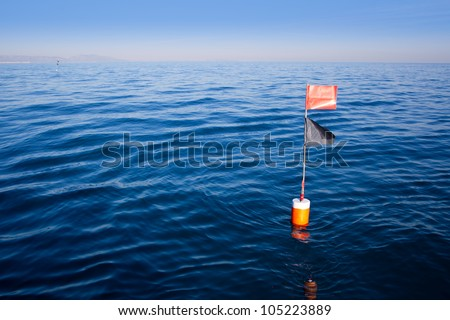 Longliner and trammel net buoy with flag pole in blue sea - stock photo