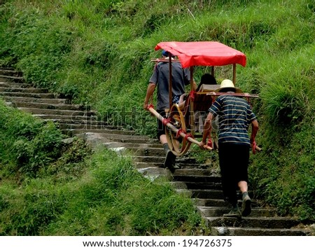 Longsheng, China - May 2, 2006:  Porters carry a tourist seated in a covered sedan chair up a steep flight of stone stairs to the ancient Yao village of Ping-An in China's Guang Xi Province - stock photo