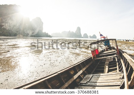 Longtail boat stuck on Tonsai beach due to low tide. - stock photo