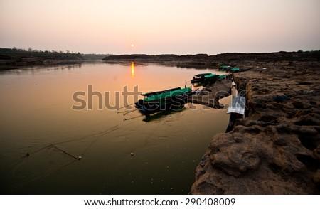 Longtail boat, Sunset Berth at sand Sam Pan Bok Grand Canyon in Maekhong river, Northeast of Thailand. - stock photo