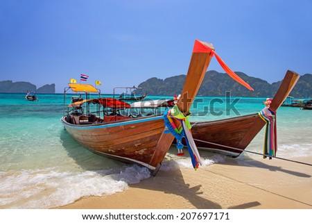 Longtail boats landing at Railay bay, Krabi province, Thailand - stock photo